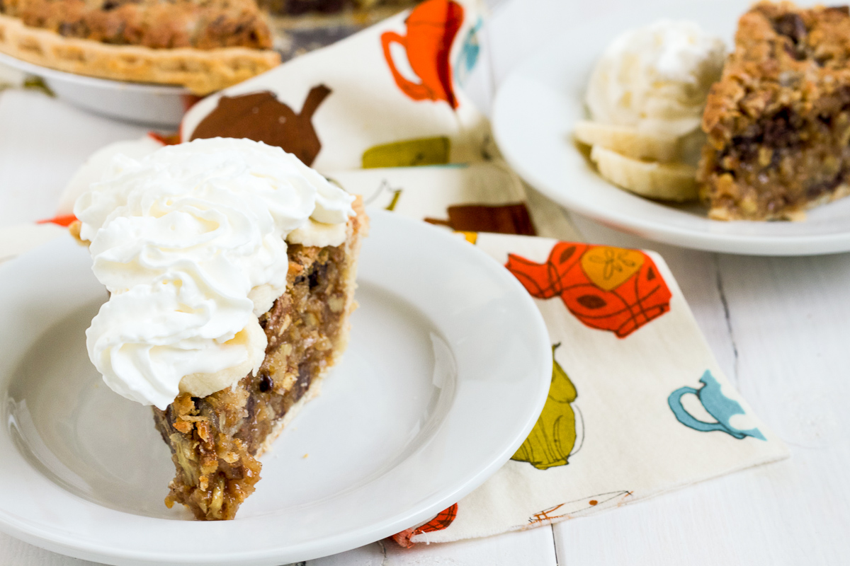 Sawdust Pie is filled with chocolate chips, pecans, shredded coconut, and graham cracker crumbs. Topped with banana slices and fresh whipped cream, it makes a delicious addition to the Thanksgiving dessert table!